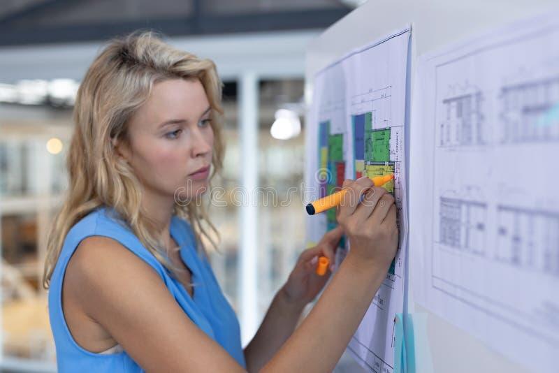 Arquiteto fêmea que trabalha sobre o modelo no whiteboard em um escritório moderno fotos de stock