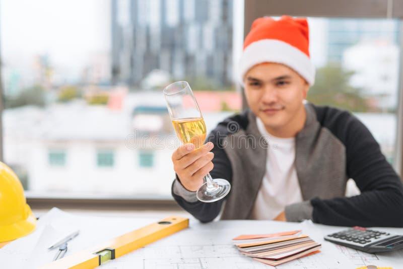 Arquiteto feliz que comemora o ano novo feliz com copos de vinho imagem de stock