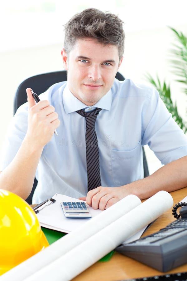 Arquiteto masculino considerável que estuda um projeto imagem de stock