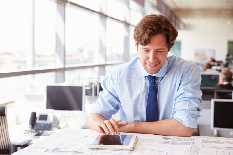Arquiteto masculino que usa o tablet pc em uma mesa em um escritório foto de stock royalty free