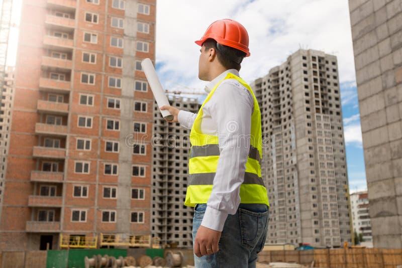Arquiteto no capacete de segurança que aponta com os modelos rolados na construção fotos de stock