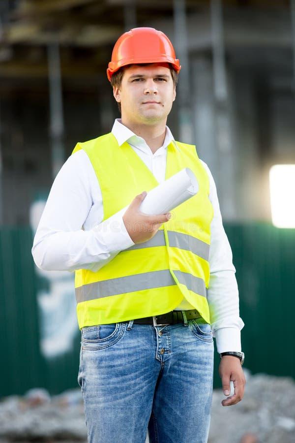 Arquiteto no capacete de segurança que levanta com os modelos contra o andaime fotografia de stock royalty free