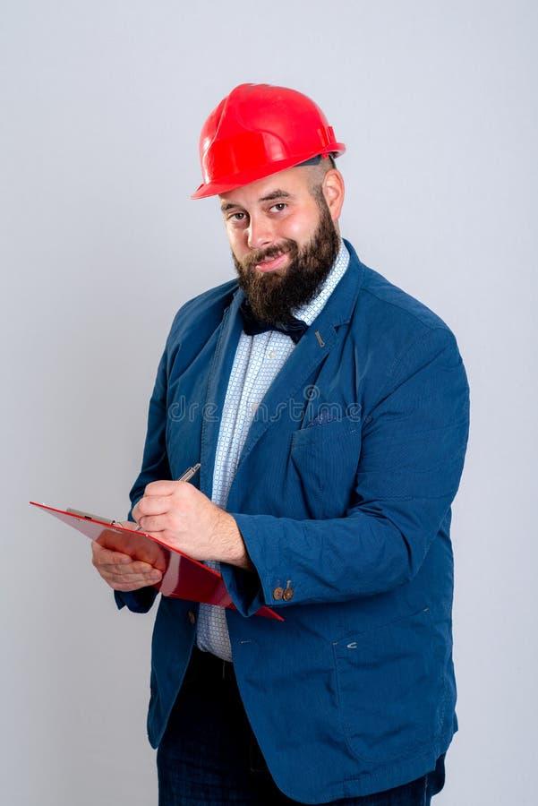Arquiteto novo com capacete e a prancheta vermelhos imagens de stock royalty free