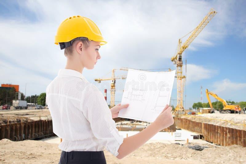 Arquiteto novo da mulher de negócio no capacete amarelo do construtor com bui fotografia de stock