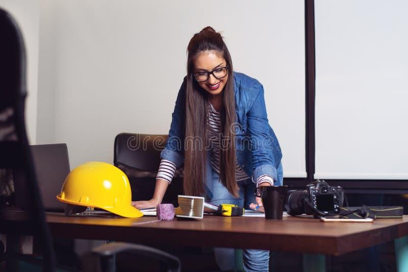 Arquiteto novo que olha papéis antes de ir fora no canteiro de obras - Imagem imagens de stock