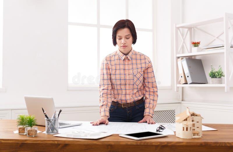 Arquiteto novo que trabalha com os modelos no escritório imagem de stock royalty free
