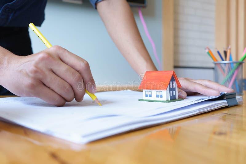 Arquiteto ou coordenador que usa o lápis amarelo que trabalha no modelo no local de trabalho - projeto arquitetónico, conceito da foto de stock