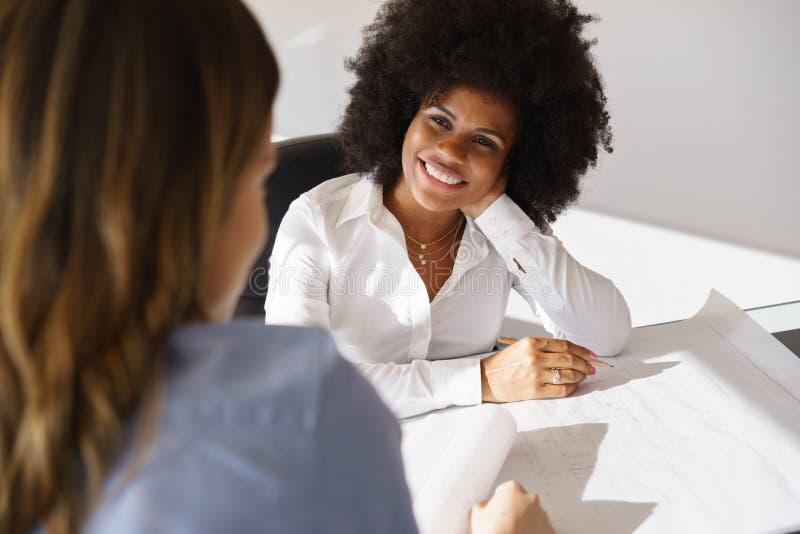 Arquiteto preto Women Talking Plans e habitação social fotografia de stock royalty free