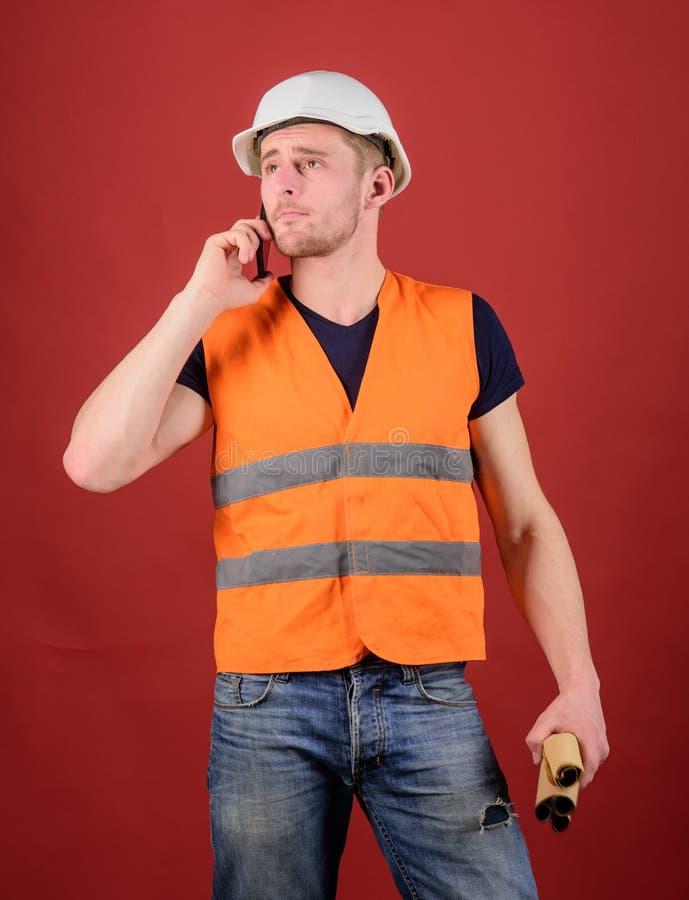 Arquiteto que chama o coordenador para fixar o plano Conceito de uma comunicação Homem, contramestre no capacete que fala no tele foto de stock