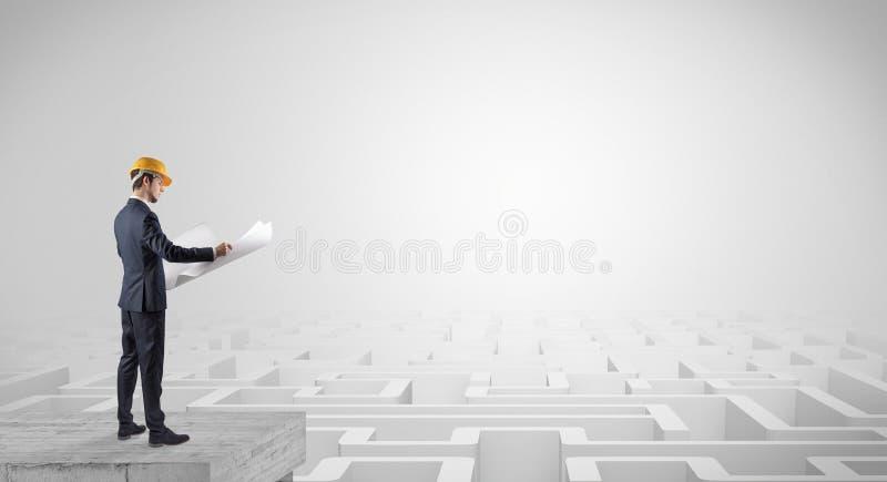 Arquiteto que est? sobre um labirinto e que guarda um plano imagem de stock
