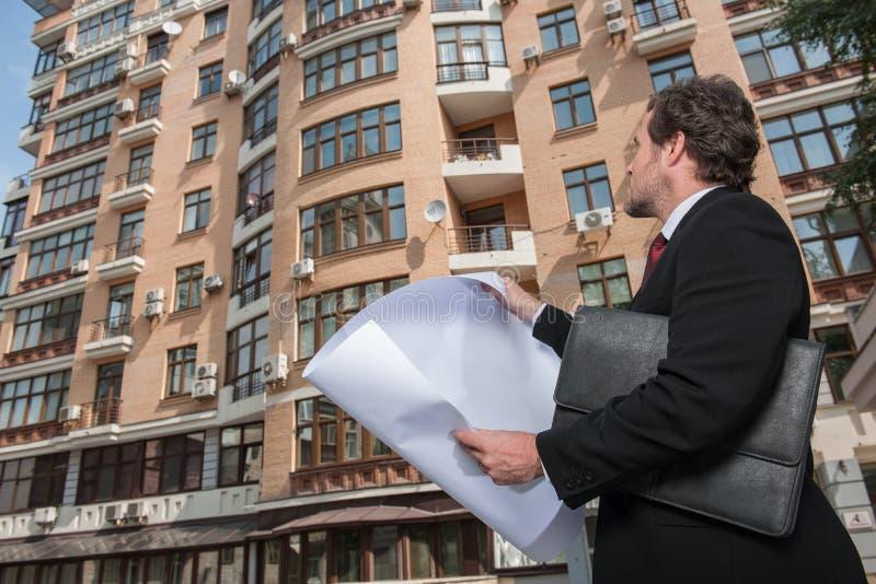 Arquiteto que olha o plano e o prédio de apartamentos fotografia de stock