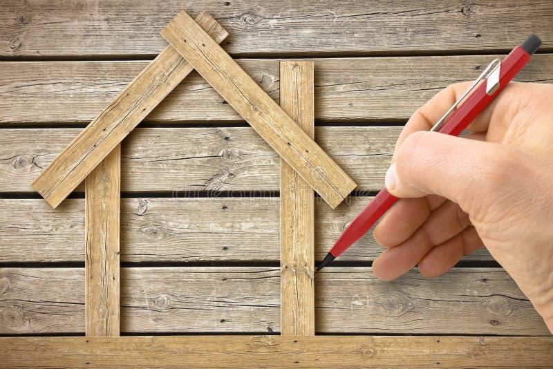 Arquiteto que tira uma casa de madeira conceptual no fundo de madeira - imagem do conceito imagem de stock royalty free