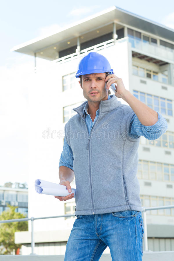 Arquiteto que usa o telefone celular fora da construção foto de stock