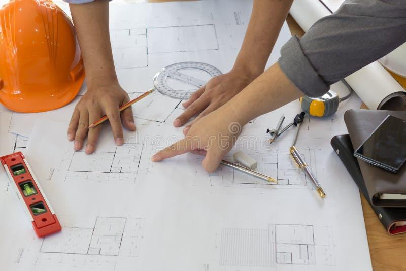 Arquiteto Working On Blueprint Local de trabalho dos arquitetos - projeto arquitetónico, modelos, régua, calculadora, portátil e  fotografia de stock royalty free