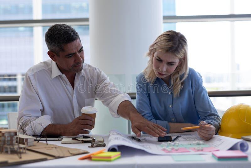 Arquitetos caucasianos que discutem sobre o modelo na mesa no escritório fotografia de stock royalty free
