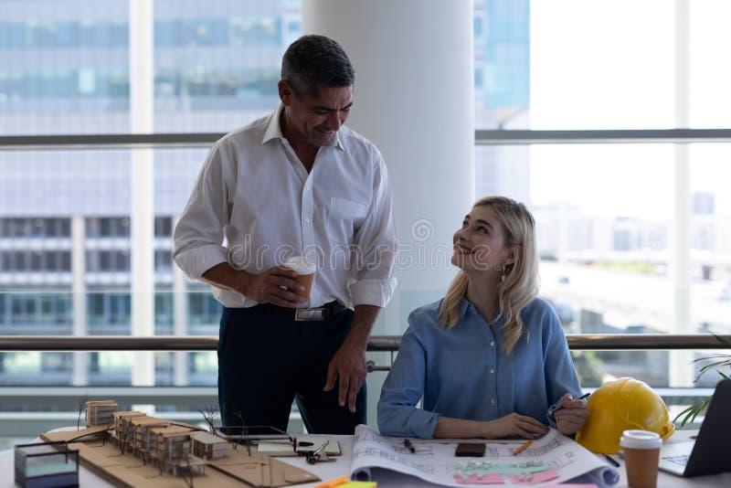 Arquitetos dos Caucasians que interagem um com o otro na mesa no escritório imagens de stock