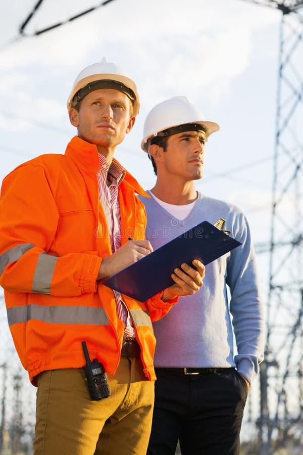 Arquitetos masculinos com a prancheta que inspeciona o local junto imagem de stock