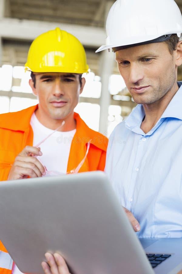 Arquitetos masculinos que trabalham no portátil no canteiro de obras imagens de stock
