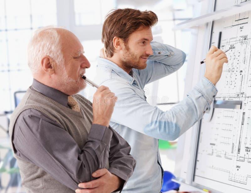 Arquitetos novos e superiores que trabalham junto imagem de stock