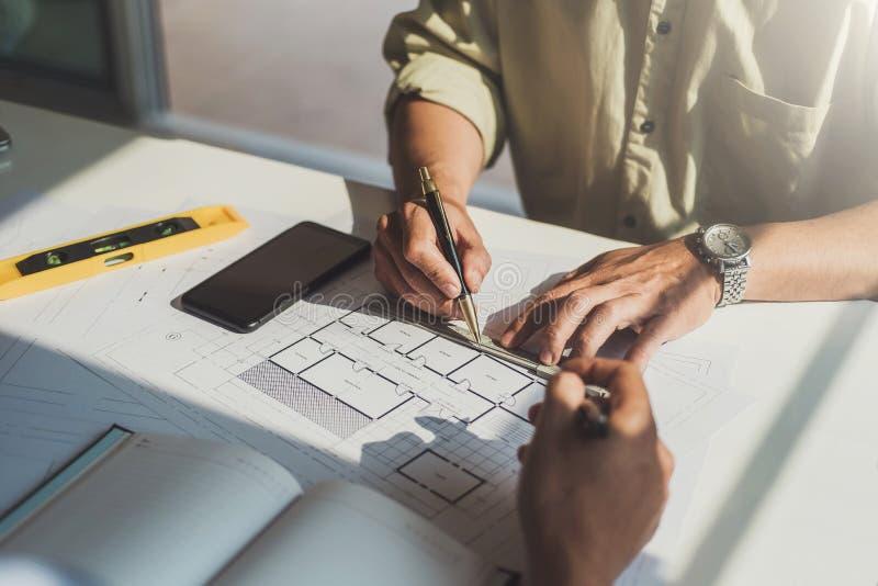 Arquitetos ou construção do coordenador que discute sobre o projeto de design de interiores com os modelos no local de trabalho d imagem de stock