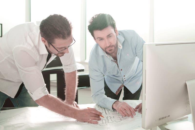 Arquitetos que trabalham com os desenhos no escritório imagens de stock