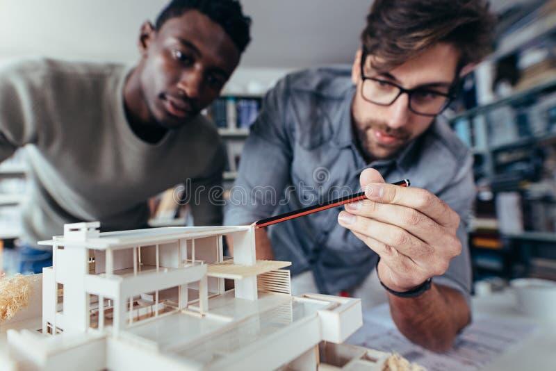 Arquitetos que trabalham no modelo arquitetónico novo da casa foto de stock