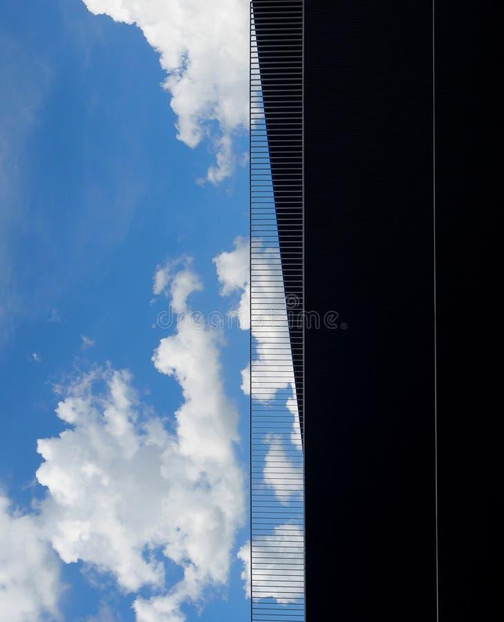 Arquitetura abstrata do fundo Uma cerca vertical do metal divide uma obscuridade - construção azul de um céu azul do verão com nu imagens de stock