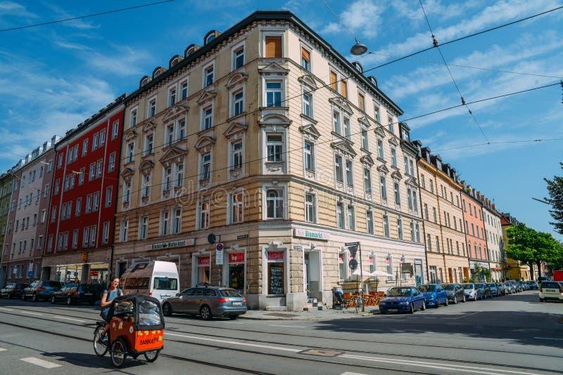 Arquitetura bávara tradicional no centro de Munich em um dia ensolarado A mulher dá um ciclo em um carro do impulso com suas cria foto de stock
