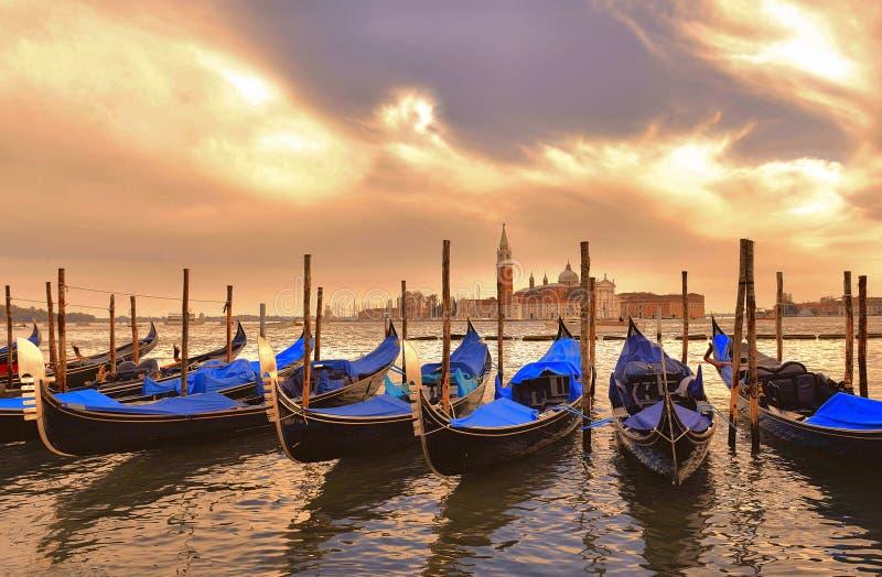 Arquitetura da cidade com as gôndola azuis de Veneza nas docas quadradas de St Mark e cloudly o por do sol na ilha do St Giorgio  imagens de stock royalty free
