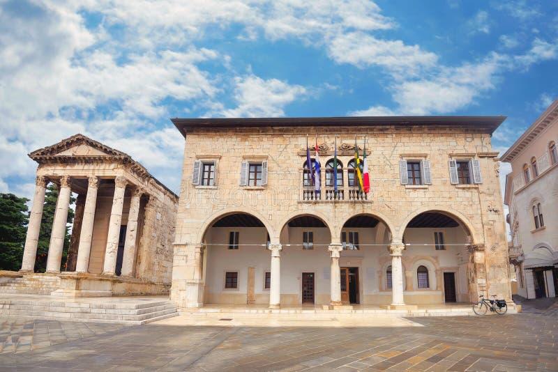 Arquitetura da cidade com a câmara municipal comunal do palácio e o templo antigo de Augustus nos Pula Istria, Croatia fotografia de stock
