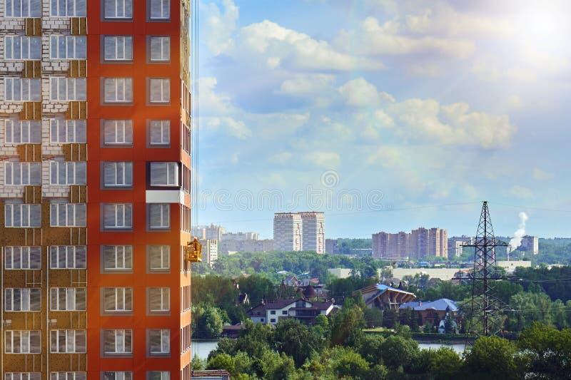 A arquitetura da cidade de Moscou com um trabalhador em um berço da construção na parede de uma construção sob a construção ilumi fotografia de stock royalty free