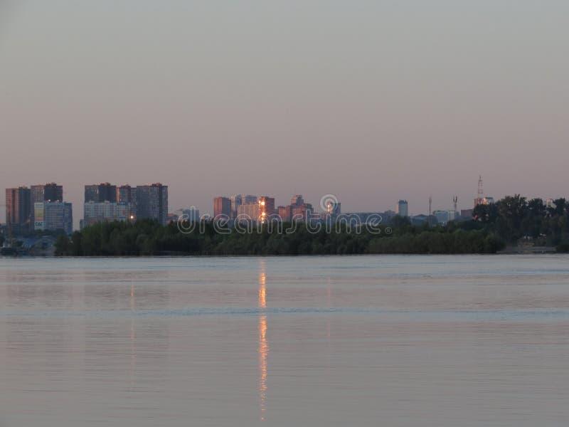 Arquitetura da cidade do alvorecer com reflexão na água do rio do alargamento alaranjado brilhante na janela da casa fotos de stock royalty free