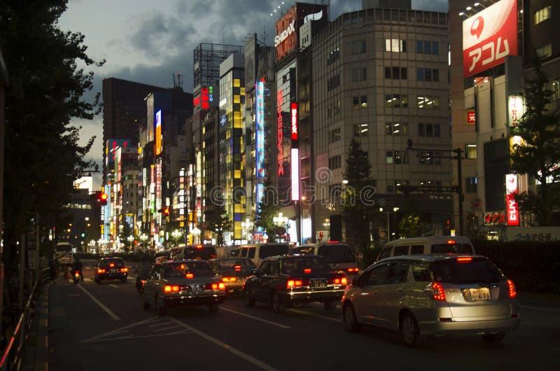 A arquitetura da cidade e o povo japonês conduzem o carro na estrada do tráfego no crepúsculo fotografia de stock