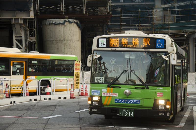 A arquitetura da cidade e o povo japonês conduzem o ônibus na estrada do tráfego e param-no imagem de stock