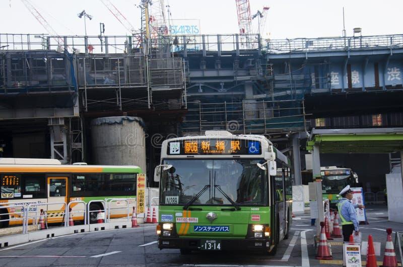 A arquitetura da cidade e o povo japonês conduzem o ônibus na estrada do tráfego e param-no imagens de stock royalty free