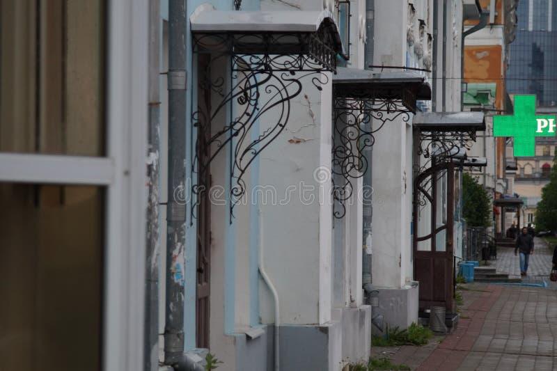 Arquitetura da cidade: fragmentos de casas antigas na rua de Pushkin Moldação e elementos forjados da decoração das construções foto de stock