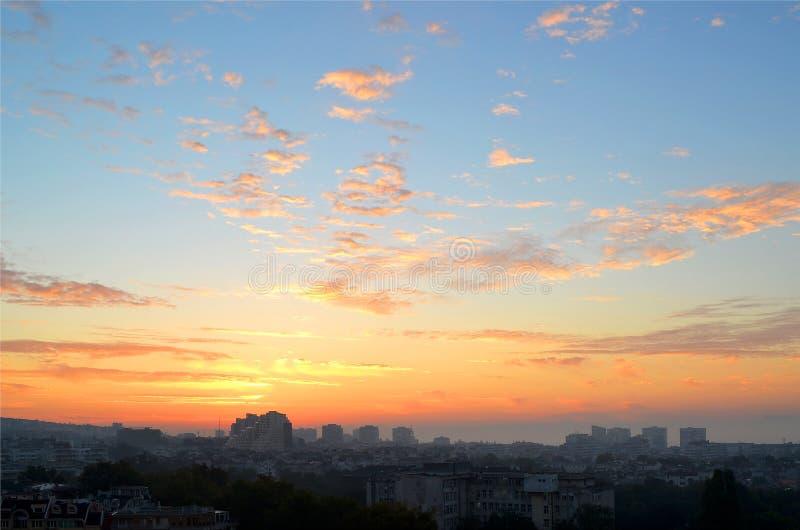 Arquitetura da cidade no amanhecer: nuvens cor-de-rosa e alaranjadas em um céu azul no alvorecer imediatamente antes do nascer do imagens de stock royalty free