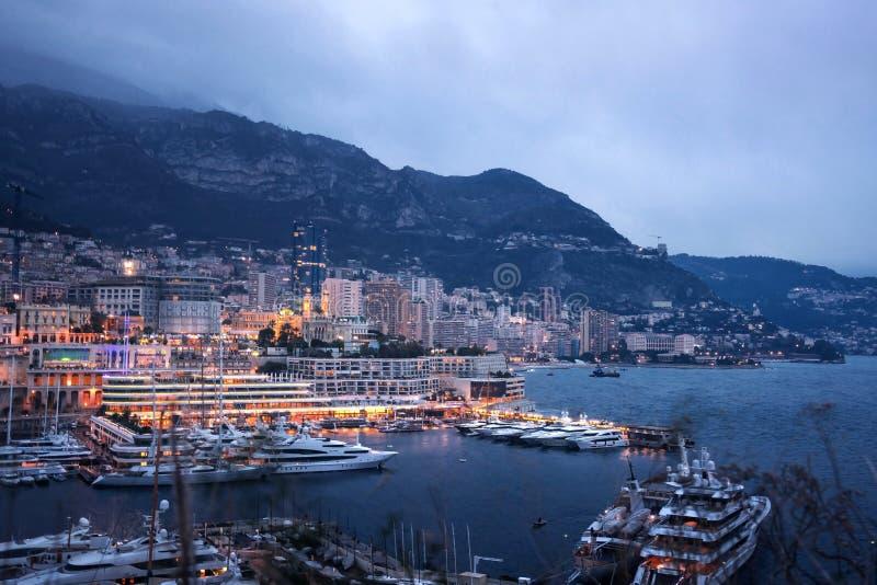 Arquitetura da cidade da noite de Monte - Carlo pelo porto, riviera de Mônaco março imagens de stock