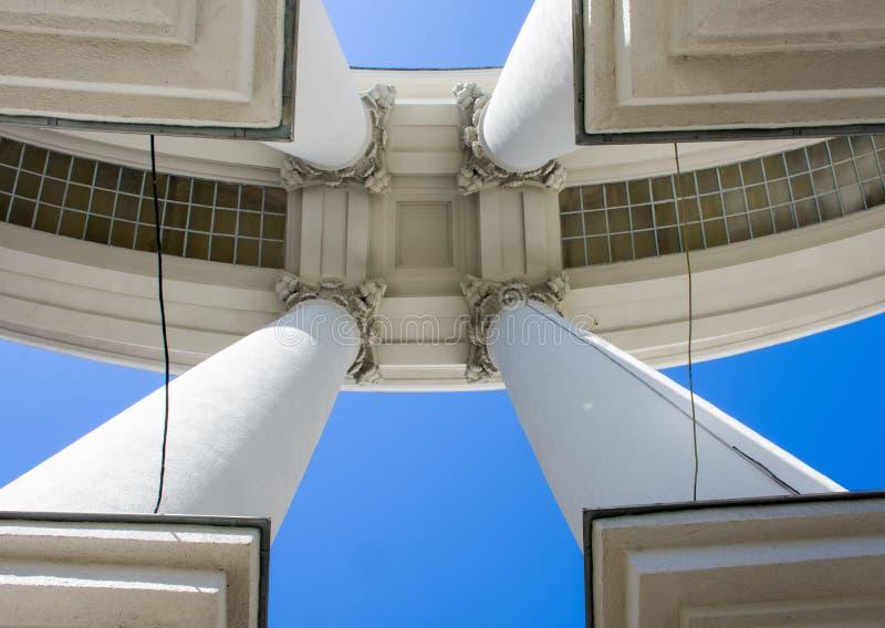 A arquitetura do estilo do império Quatro colunas concretas grandes com bases nos cantos da foto mantêm o telhado contra o b foto de stock