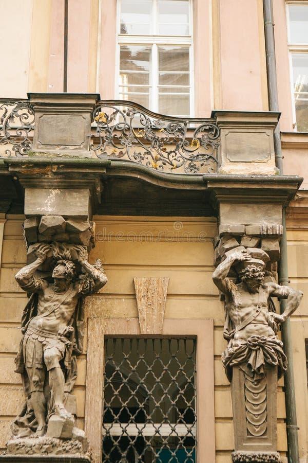 Arquitetura europeia Close-up - esculturas - colunas sob a forma dos caráteres antigos que apoiam o balcão - fachada de foto de stock royalty free