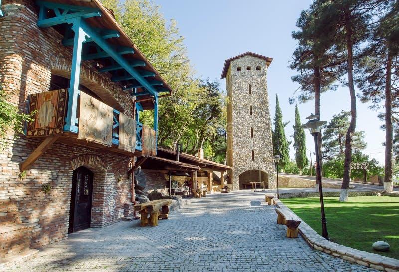 Arquitetura Georgian tradicional com torre do tijolo, a casa rural e o parque imagem de stock royalty free
