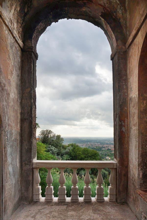 Arquitetura medieval Grande arco na parede com um banister e uma bela paisagem italiana foto de stock royalty free