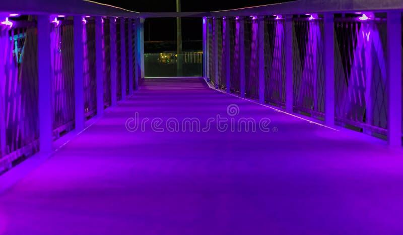 Arquitetura moderna de passeio iluminada roxa de néon da estrada da ponte em scheveningen uma cidade popular nos Países Baixos imagens de stock