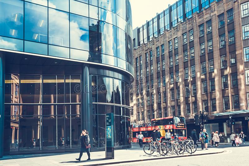 Arquitetura moderna, de vidro com construção velha, bicicletas e povos que andam no centro de Glasgow fotos de stock royalty free