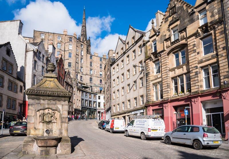 Arquitetura tradicional e lojas coloridas ao longo de uma rua de encurvamento em Edimburgo e no céu azul fotografia de stock royalty free
