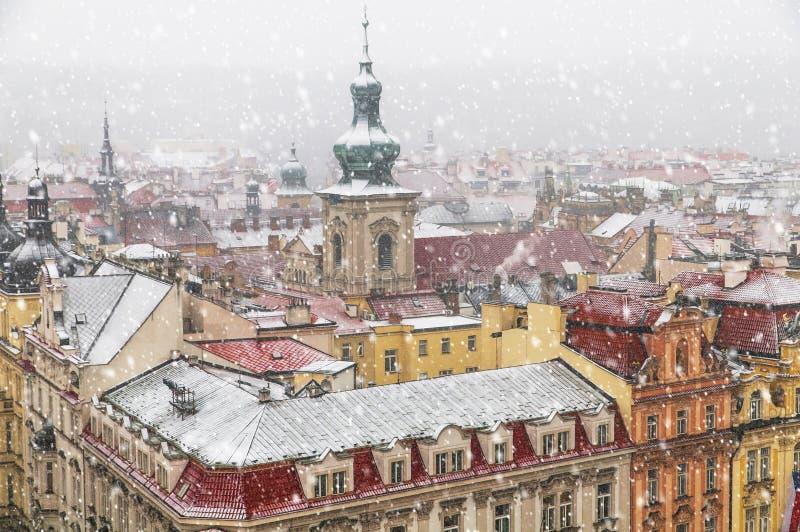 A arquitetura velha de Praga e os telhados vermelhos veem de cima na queda de neve do inverno imagens de stock