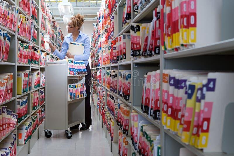 Arquivamento da mulher em arquivos do hospital foto de stock royalty free