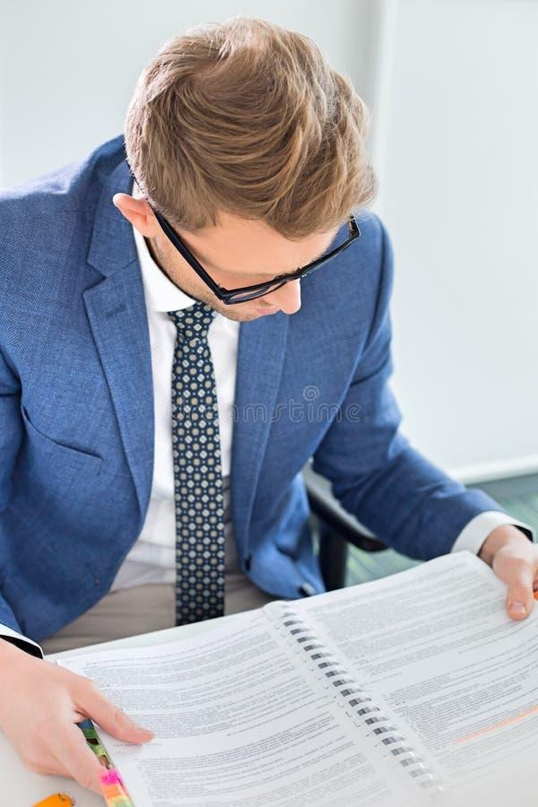 Arquivo criativo da leitura do homem de negócios na mesa no escritório fotografia de stock