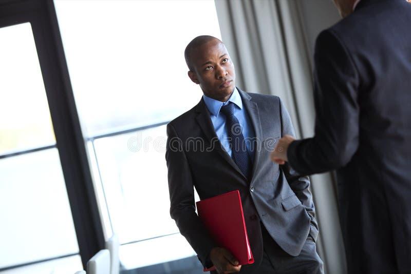 Arquivo de terra arrendada novo do homem de negócios ao escutar o colega masculino no escritório fotos de stock
