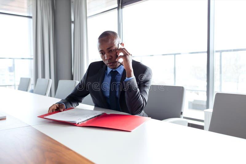 Arquivo de terra arrendada novo do homem de negócios ao falar no telefone na tabela de conferência fotografia de stock